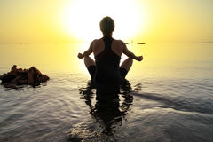 Woman in lotus pose at sunrise Stock Photos