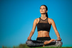 Woman in lotus position. Attractive young woman in a lotus position in green park Royalty Free Stock Images