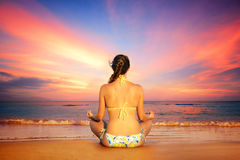 Woman in lotus position on a background of sunset Royalty Free Stock Images