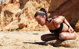 Woman in lotus position at the sand beach Stock Photo