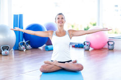 Woman in lotus posture with arms outstretched. In fitness studio Royalty Free Stock Photo