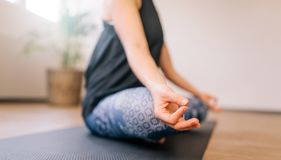 Woman in lotus yoga pose indoors Stock Photography