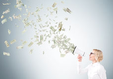 Woman with loudspeaker. Beautiful woman with white loudspeaker, dollars flying from it. Side view. Grey background. Concept of informing about success stock images
