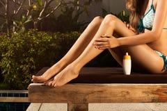 Woman on lounge and moisturizing her skin Stock Photo