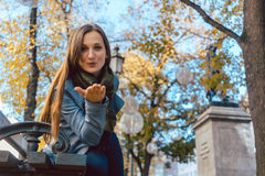 Woman in love blowing kiss in autumn park. Towards viewer Royalty Free Stock Image