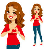 Woman Love Sign. Beautiful brunette making love heart symbol with her hands on top of a red shirt Stock Photo