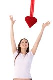 Woman in love trying to reach red heart smiling. Young woman in love, jumping to reach red heart at valentines day Royalty Free Stock Photo