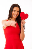 Woman in love wearing red dress holding red heart sending messag Stock Images