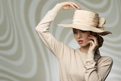 Woman with lovely hat. Cute elegant vogue girl wearing coordinated beige hat and dress, in fashion pose with romantic expression Stock Photos