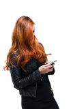 Woman with lovely red hair texting on a smartphone Royalty Free Stock Image