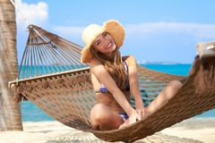 Woman with lovely smile sitting in a hammock. Gentle gracious woman with lovely smile sitting in her straw sun hat and bikini in a hammock on a tropical beach Stock Images