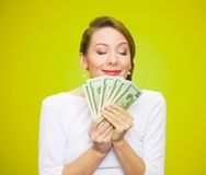 Woman loves money. Hungry for money. Portrait, greedy executive, CEO, boss, corporate employee, holding, smelling dollar banknotes tightly, isolated green royalty free stock photography