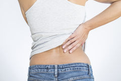 Woman with lower back pain. Rear view of a woman with lower back pain clutching her hands to her back and spine to relieve the ache in her muscles or spinal Stock Image