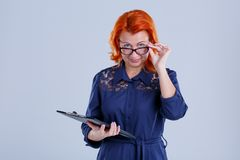 The woman lowered her glasses with a writing-table in her hand against a gray background. A woman, aged with red hair in a blue dress, lowered her glasses with a Royalty Free Stock Photography