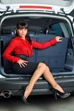 Woman in luggage compartment. Beautiful girl sitting in luggage compartment of car Royalty Free Stock Images