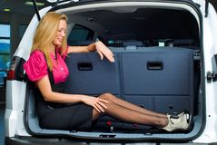 Woman in luggage compartment. Beautiful girl sitting in luggage compartment of car Stock Photos