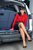 Woman in luggage compartment. Beautiful girl sitting in luggage compartment of car Stock Images
