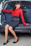 Woman in luggage compartment. Beautiful girl sitting in luggage compartment of car Royalty Free Stock Photography