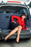 Woman in luggage compartment. Beautiful girl sitting in luggage compartment of car Stock Image