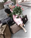 Woman with luggage flowers and dog Royalty Free Stock Photo