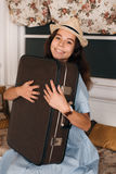 Woman with luggage get ready to travell. Young smiling woman with luggage sitting on sofa Stock Images