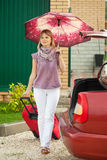 Woman with luggage go to car. Happy woman with luggage go to car from home Royalty Free Stock Photos