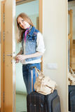 Woman with luggage loocking door Stock Image