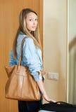 Woman with luggage near door Stock Photos