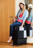 Woman with luggage near door Royalty Free Stock Photo
