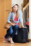 Woman with luggage near door Royalty Free Stock Image