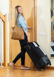 Woman with luggage near door Royalty Free Stock Photos