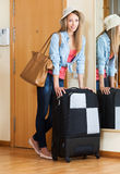 Woman with luggage near door Stock Image