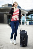 Woman With Luggage Talking On Mobile Phone Outside Railroad Stat Stock Image