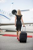 Woman With Luggage Walking Towards Private Jet. Rear view of wealthy woman with luggage walking towards private jet at airport terminal Royalty Free Stock Photography