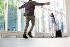 Woman with luggage waving to boyfriend at airport Stock Photography