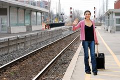 Woman with luggage waving at train station Royalty Free Stock Image