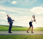 Woman lugging man on the road Stock Photo