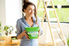 Woman with lunch boxes. Portrait of a young smiling woman with green lunch boxes indoors stock photography