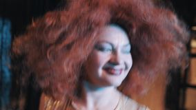 Woman in lush rufous hair wig grimacing and dancing on scene with troupe. Woman in lush rufous hair wig grimacing for camera and dancing on scene with troupe stock video footage