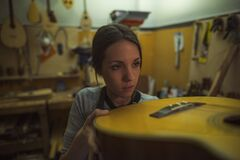 A woman luthier checking the construction quality of a classic guitar in her musical instrument workshop
