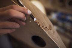 Woman luthier is making a tambur in her musical instrument workshop