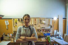Woman luthier small business owner portrait, in her musical instrument workshop