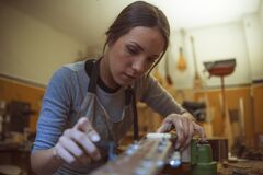 A woman luthier is tuning a classic guitar in her musical instrument workshop