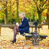 Woman in the Luxembourg garden of Paris on a fall day, drinking coffee to go. Beautiful young woman in the Luxembourg garden of Paris on a fall day, drinking royalty free stock image