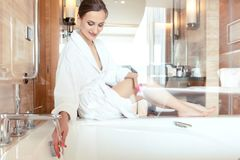 Woman in luxurious hotel bathroom letting water in the bathtub. In animation of a relaxing experience stock photo