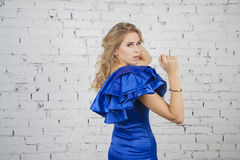 Woman in luxurous blue dress poses Royalty Free Stock Images