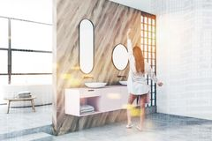 Woman in luxury bathroom with pink double sink. Woman in nightgown standing in modern bathroom with white and wooden walls, panoramic windows and white bathtub royalty free stock image