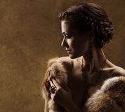 Woman in luxury fur coat, retro vintage style. Woman in luxury fur coat. Vintage style. Brown background Royalty Free Stock Photography