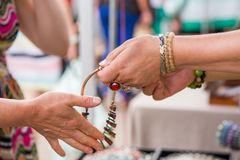 Woman with luxury gemstone rings and bracelets selling expensive jewelry. Shot of reaching hand for a necklace royalty free stock images