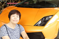 Woman and luxury sports car. Chinese middle-aged woman and yellow luxury sports car Stock Photography